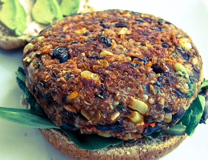 a black bean and corn burger cooked on an open burger bun with avocado in the background