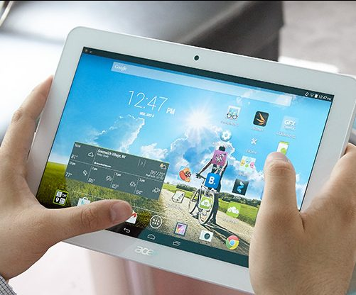 a pair of hands holding a white tablet on the main screen is the time and a blue sky and green grass picture