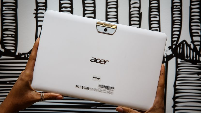 a pair of hands holding up the white acer tablet with the back of it facing the camera
