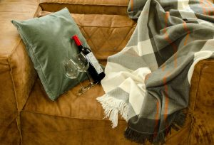 a brown sofa with a black white and grey plaid blanket with a wine bottle and two glasses on it