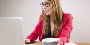 A blonde woman with straight hair to her shoulders wearing black rimmed glasses in a red jacket typing at a white laptop on a wooden table reaching for a white mug with a foamy coffee in