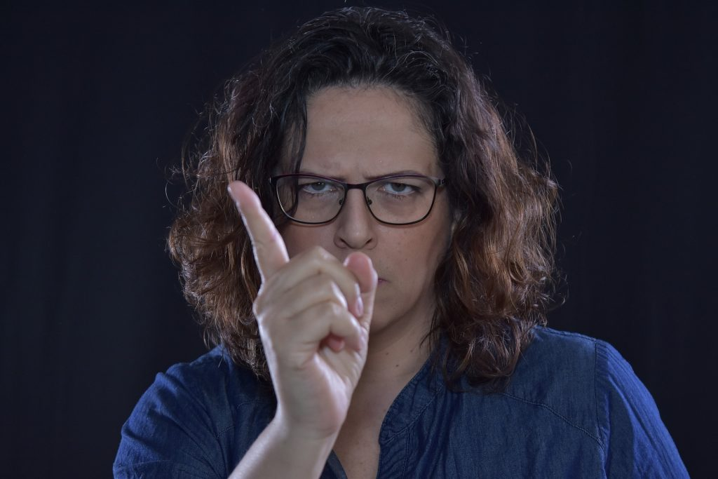 a woman with brown curly hair at shoulder level wearing black rimmed square glasses scowling at the camera and holding up a finger and wagging it
