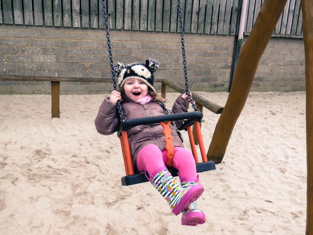 alyssa smiling at the camera on a swing