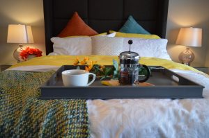 a photo from the bottom of a bed looking up. white bedlinen and orange and turquoise cushions with a black head board. yellow and green blanket. a breakfast tray with toast and coffee is on the end of the bed