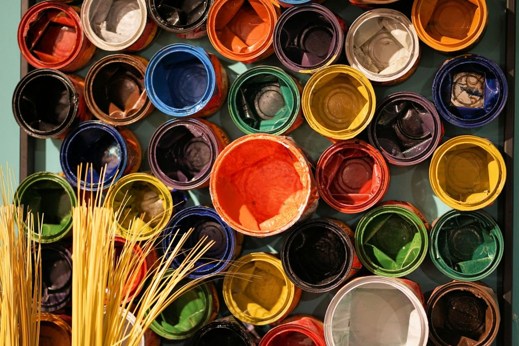 a top shot of lots of open paint tins of varying colours - orange blue yellow red green brown white