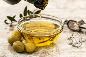 a glass bowl with olive oil in it and a bottle pouring into it with fresh olives next to the bowl