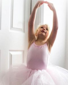 a little blonde girl in a pink tutu with arms in the air