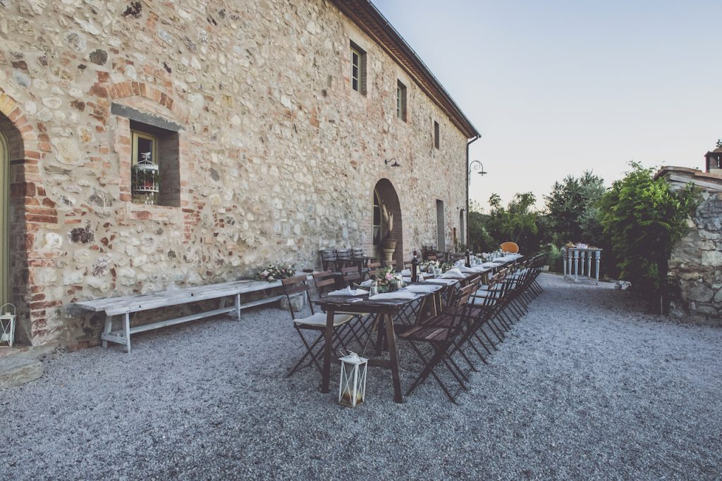 a stone building with a pebbled courtyard and a long table with chairs laid beautifully out in front of it with trees in the background