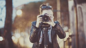 a woman in a leather jacket facing the camera holding a camera to her face