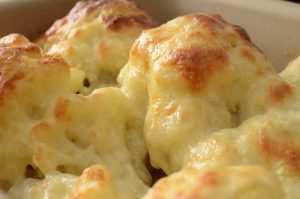 a close up of cauliflower cheese with a crispy top