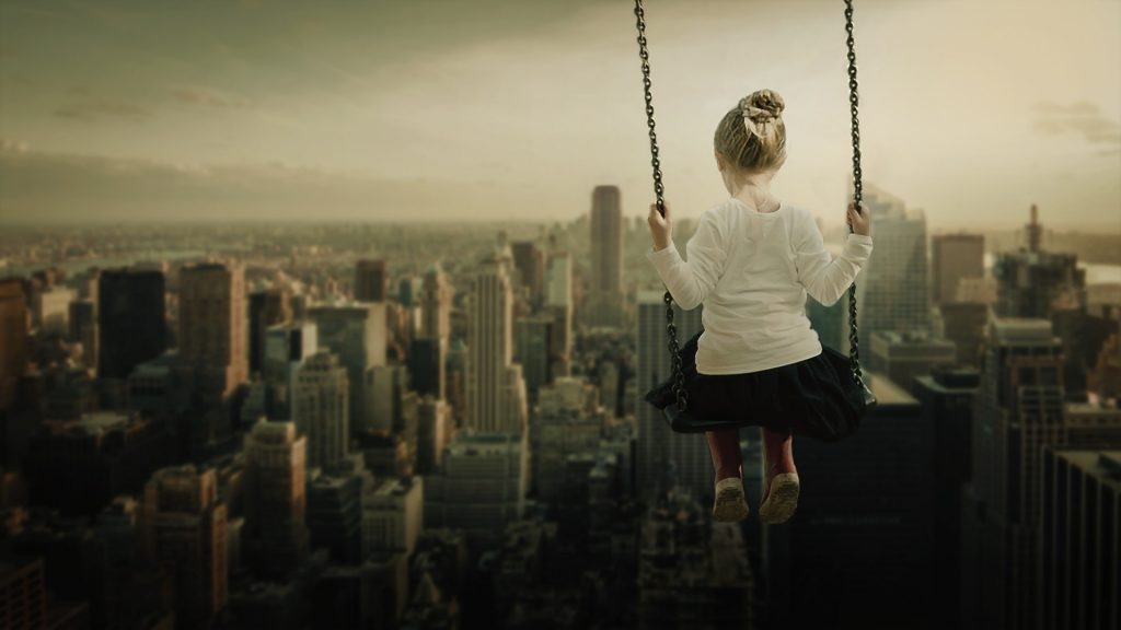 a girl facing away from the camera sat on a swing over the top of a city skyline