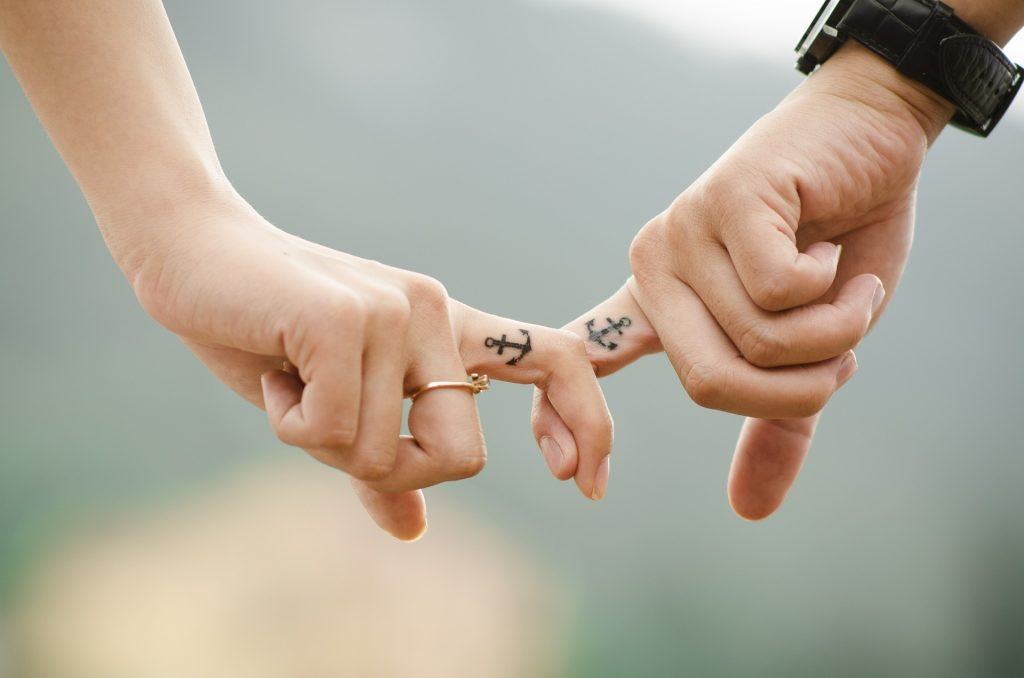 two fingers both with an anchor tattoed on holding each others finger