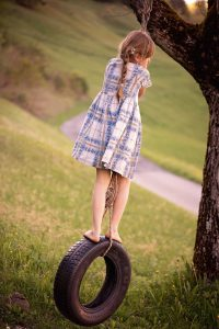 a girl stood on top of a tyre swing hanging from a tree