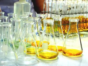a table full of glass experiment bottles with yellow liquid in