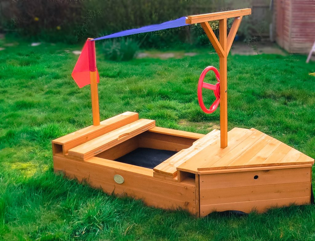a wooden childs boat with a blue sail and red flag and steering wheel with a sandpit in the centre