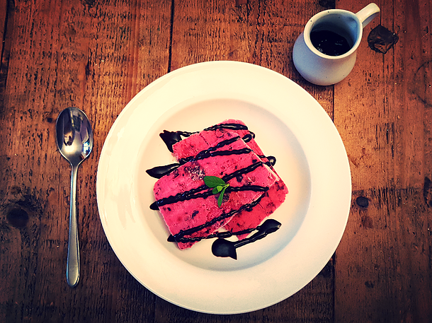 a plate with purple berry terrine and chocolate sauce on top with a spoon and a white jug with more sauce on the side