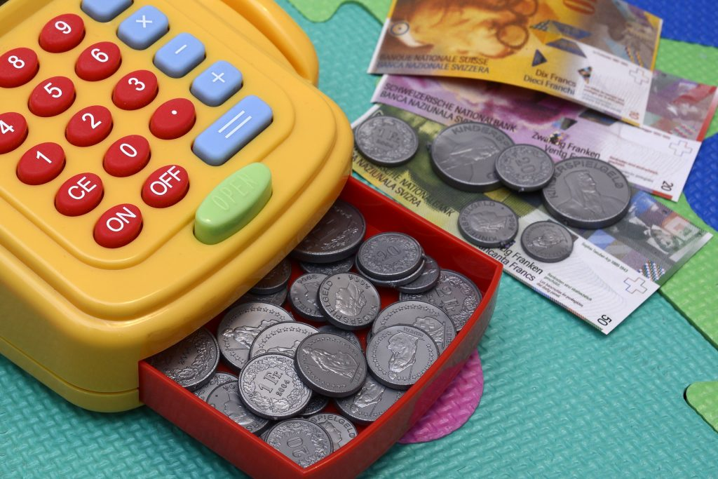 a childs toy cash register with fake coins and notes