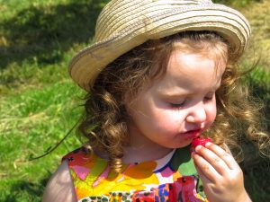 alyssa wearing a sunhat with her eyes closed enjoying a strawberry as the juice drips down her chin