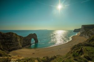 a picture of durdle door in dorset looking down on a sunny day