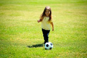 a little girl playing football on the grass