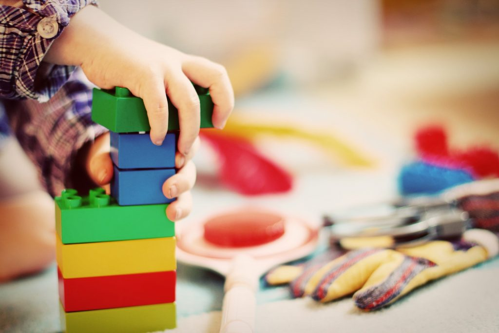 a childs hand playing with colourful building blocks
