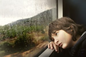 a young boy, bored, staring out of a rain covered window
