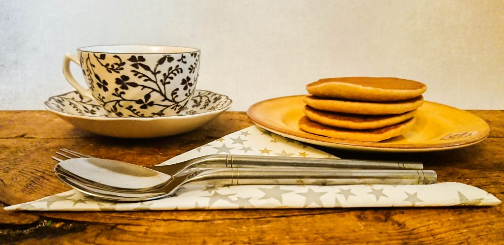 a plate with pancakes a cup and sauce and cutlery