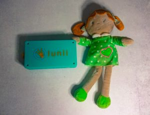 the lunii my fabulous storyteller device next to a dolly
