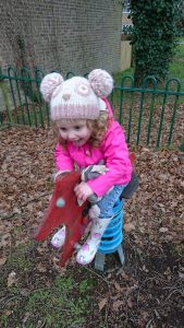 Alyssa riding a spring horse in a park wearing a hat and coat in winter dorset