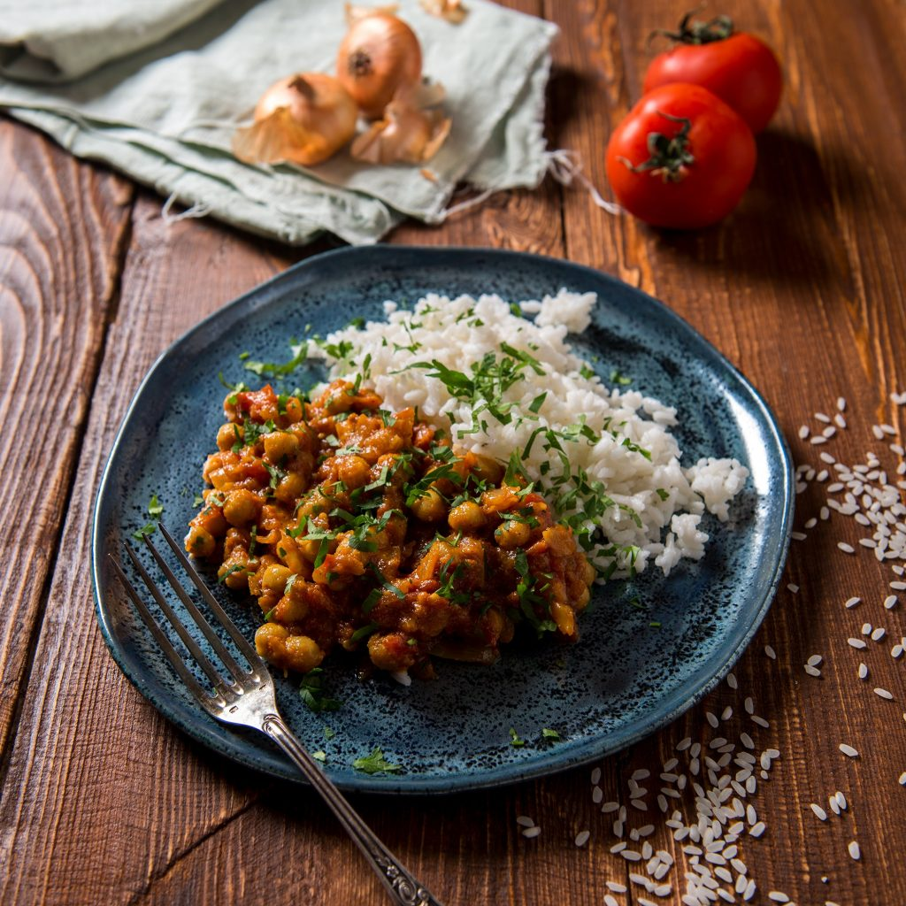 a plate of vegan chickpea curry with rice on a wooden table