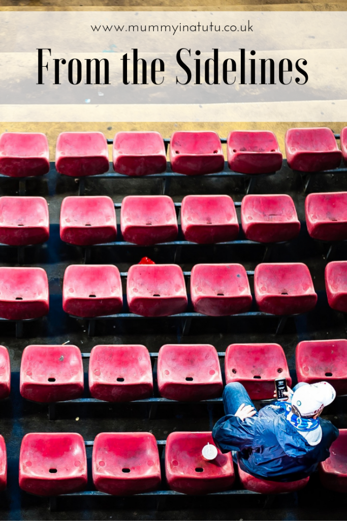 red spectator seats with a single person in them