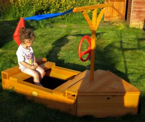 alyssa sat in a wooden sandpit in the shape of a boat at sunset