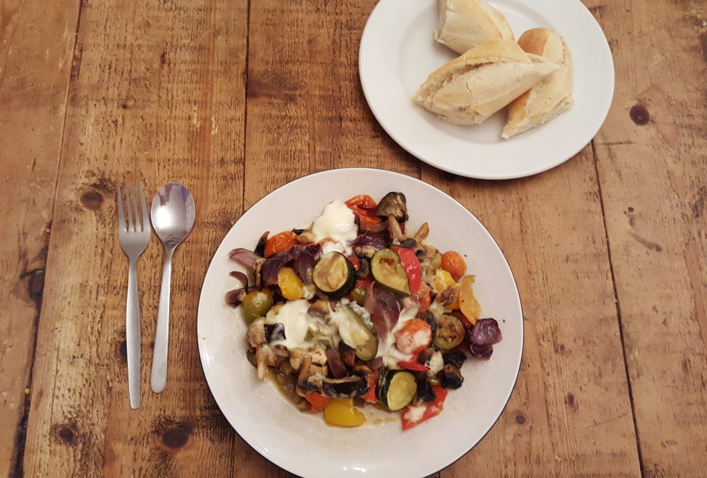 a plate of med veg with a plate of bread on a wooden table