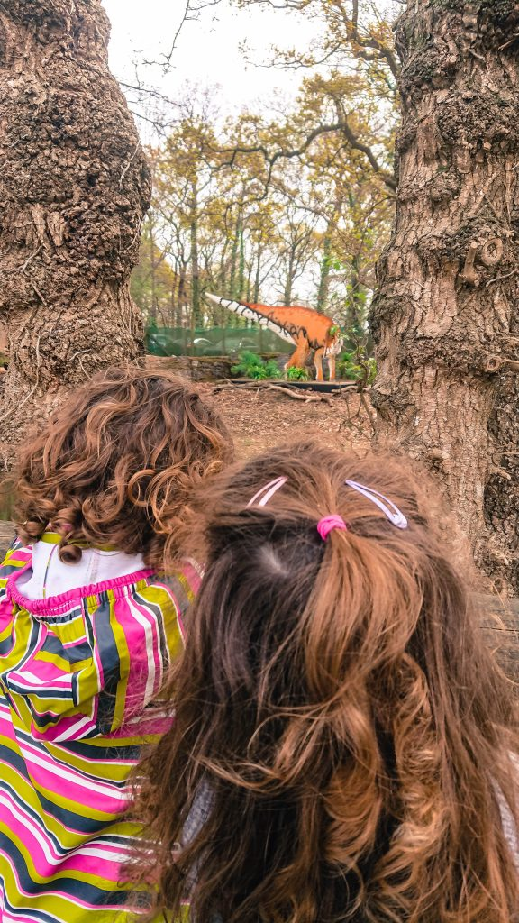 The two girls looking through the trees at a brickosaur
