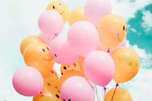 a bunch of pink and orange balloons
